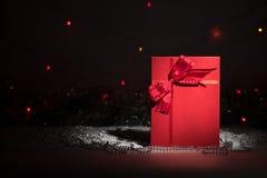 Gåvaask med den röda pilbågen på abstrakt bakgrund Fotografering för Bildbyråer