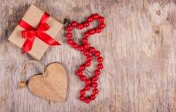 Gåvaask med den röda pilbågen, valentin och korallhalsbandet på den gamla träbakgrunden St Dag för valentin` s kopiera avstånd Royaltyfri Bild