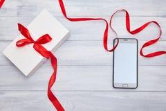 Gåvaask med det röda bandet och smartphone på en woodembakgrund fotografering för bildbyråer