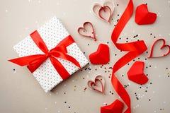 Gåvaask med det röda pilbågebandet och pappers- hjärta för röd origami på grå bakgrund för valentindag Den selektiva fokusen, läg arkivbilder