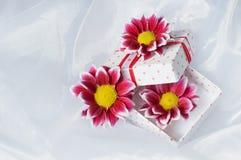 Gåvaask med det rosa bandet och blommor Arkivbild