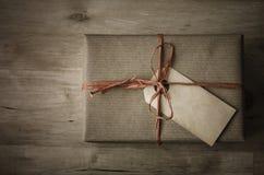 Gåvaask med enkel inpackning och den Grungy jordlottetiketten Arkivfoto