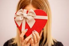 Gåvaask med ett band i kvinnliga händer Begreppet är passande för kärlekshistorier, födelsedagar och Valenti arkivbilder
