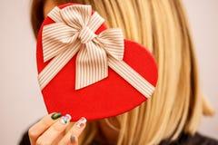 Gåvaask med ett band i kvinnliga händer Begreppet är passande för kärlekshistorier, födelsedagar och Valenti royaltyfri foto