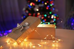 Gåvaask med felika ljus och den suddiga julgranen, inomhus Fotografering för Bildbyråer