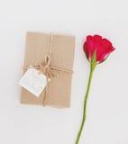 Gåvaask med rosblomman med handen som drar det vita kortet för lyckliga valentin, på vit bakgrund Arkivfoton