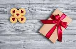 Gåvaask med satängpilbågen och kakor med marmelad i formen av hjärta En romantisk gåva Fotografering för Bildbyråer