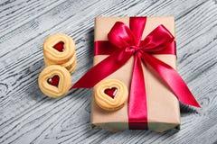 Gåvaask med satängpilbågen och kakor med marmelad i formen av hjärta En romantisk gåva Arkivfoton