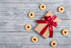 Gåvaask med satängpilbågen och kakor med marmelad i formen av hjärta En romantisk gåva Gåva på en grå bakgrund Royaltyfri Fotografi