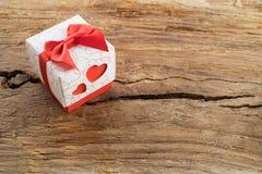 Gåvaask med två röda hjärtor på sida på träbakgrund royaltyfri bild