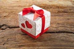 Gåvaask med två röda hjärtor på sida på träbakgrund Arkivfoto