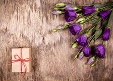 Gåvaask och bukett av blommor blommar purple Eustoma kopiera avstånd Arkivbilder