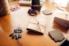 Gåvaask och handgjorda örhängen på trätabellen Arkivbilder