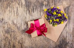 Gåvaask och lösa blommor i ett kuvert Ferier och gåvor kopiera avstånd Arkivfoton