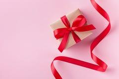 Gåvaask och rött band på rosa pastellfärgad bakgrund för valentindagkort lekmanna- stil för lägenhet arkivbilder