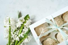 Gåvaask och vita blommor på den lantliga tabellen för dag för mars 8, internationella kvinnors, födelsedag- eller moderdagen som  Royaltyfria Foton