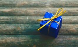 Gåvaask på lantlig träbakgrund Gåva i blått inpackningspapper Arkivbild