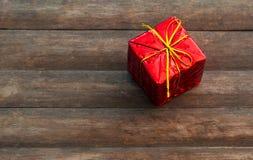 Gåvaask på lantlig träbakgrund Gåva i rött inpackningspapper Arkivfoto