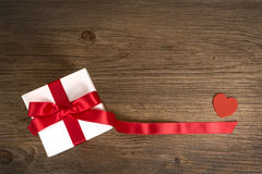 Gåvaask på träbakgrunden rött band red steg Royaltyfri Fotografi
