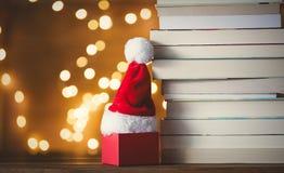 Gåvaask, Santa Claus hatt och hög av böcker Royaltyfria Foton
