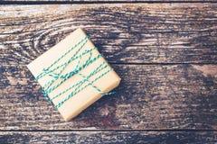 Gåvaask som packas i kraft papper med ett grönt vitt rep Gåva på lantlig träbakgrund, kopieringsutrymme Semestra gåva i tappning  royaltyfria bilder