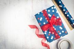 Gåvaask som slås in i blått pruckit papper med det röda bandet på en vit wood gammal bakgrund Inpackningsmaterial spridda över ta Royaltyfri Bild
