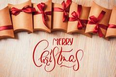 Gåvaask som slås in i kraft papper med bandpilbågen och glad jul för text Kalligrafibokstäver fotografering för bildbyråer