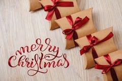 Gåvaaskar av kraft papper med röd glad jul för band och för text Letterig kalligrafi royaltyfri fotografi