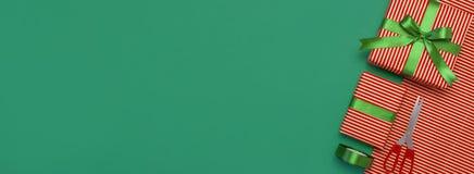 Gåvaaskar, emballagepapper, sax, band på grön bakgrund Festlig bakgrund, lyckönskan, gåvainpackning, jul och arkivbild