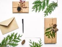 Gåvaaskar i ecopapper och en bokstav på vit bakgrund Jul eller annan feriebegrepp, bästa sikt, lekmanna- lägenhet royaltyfri bild