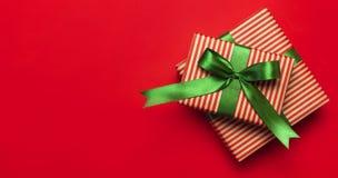 Gåvaaskar med det gröna bandet på den lekmanna- röda lägenheten för bästa sikt för bakgrund Semestra begreppet, det nya året elle arkivbild