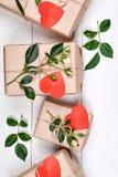 Gåvaaskar med nya rosor och röda hjärtor Royaltyfria Bilder