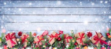 Gåvaaskar och dekorerad gran förgrena sig på den snöig tabellen Arkivbilder
