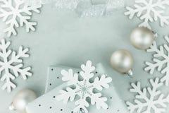 Gåvaaskar som slås in i silverpapper Krullat silverband Julstruntsaker, snö flagar ordnat i ram Kopiera utrymme för text arkivfoton