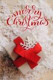 Gåvaasken av kraft papper med det röda bandet och glad jul smsar Kalligrafibokstäver arkivbilder