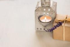 Gåvaasken med en lavendel fattar, den hjärta formade stearinljushållaren med brinnande teljus på den vita dagen för bakgrundsvale Arkivbilder