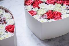 Gåvaasken med hjärta formade blommor på grå färgmarmorbakgrund royaltyfri bild