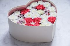 Gåvaasken med hjärta formade blommor på grå färgmarmorbakgrund royaltyfri fotografi