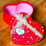 Gåvaasken med hjärtaform med inskriften älskar jag dig på träbakgrund Royaltyfri Foto