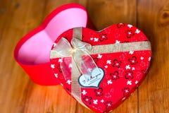 Gåvaasken med hjärtaform med inskriften älskar jag dig på träbakgrund Arkivfoton