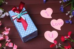 Gåvaasken och röd hjärta med trätext för ÄLSKAR JAG DIG på wood tabellbakgrund Arkivfoto