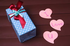 Gåvaasken och röd hjärta med trätext för ÄLSKAR JAG DIG på wood tabellbakgrund Royaltyfri Bild