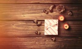 Gåvaasken och sörjer kottar med äpplen Arkivfoto
