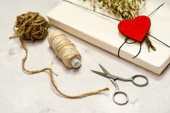 Gåvaasken som göras av kraft papper, bundet med, snör åt En träröd hjärta royaltyfri fotografi