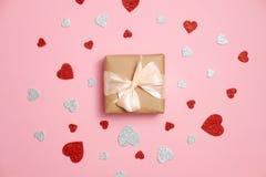 Gåvaasken som packades i kraft papper med bandpilbågen och röd och grå hjärta, formade valentin som kortet lägger på p arkivfoton