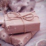 Gåvaasken som sloggs in i brunt, återanvände papper och band bästa sikt för säckrep på vit bakgrund, snöflingor Instagram Royaltyfri Bild