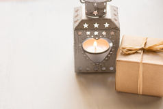 Gåvaasken, tappninghjärta formade stearinljushållaren med brinnande teljus på vit wood bakgrund, dag för valentin` s Royaltyfri Foto
