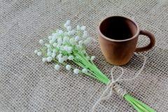 Gåvafavorit valentin för dag s Idérik lerakaffekopp och en bukett av den doftande skogliljekonvaljen på säckväv fotografering för bildbyråer