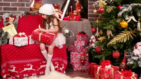 Gåvainpackning, lite flicka lägger ut kända kort för julgåvor, jultomten hjälpredan för ` som s sorterar gåvorna, flickan lager videofilmer