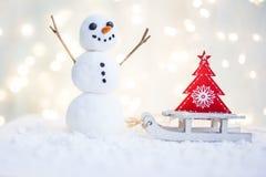 Gåvakort med ett nytt år och jul med en bild av en snögubbe med en släde mot en bakgrund av glödande girlander arkivfoto